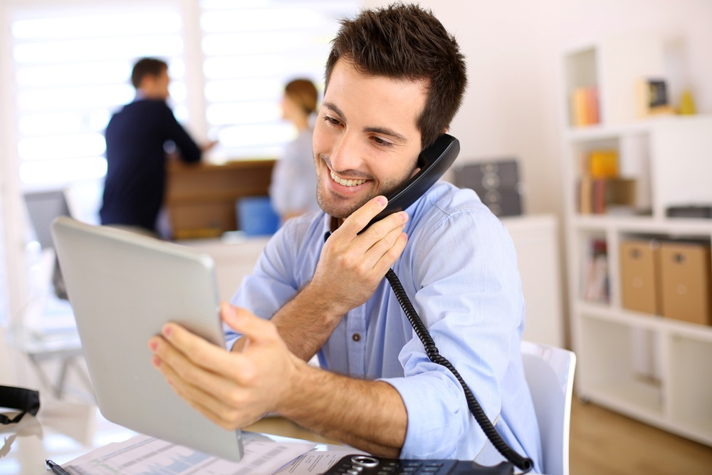Cheerful man in office answering the phone