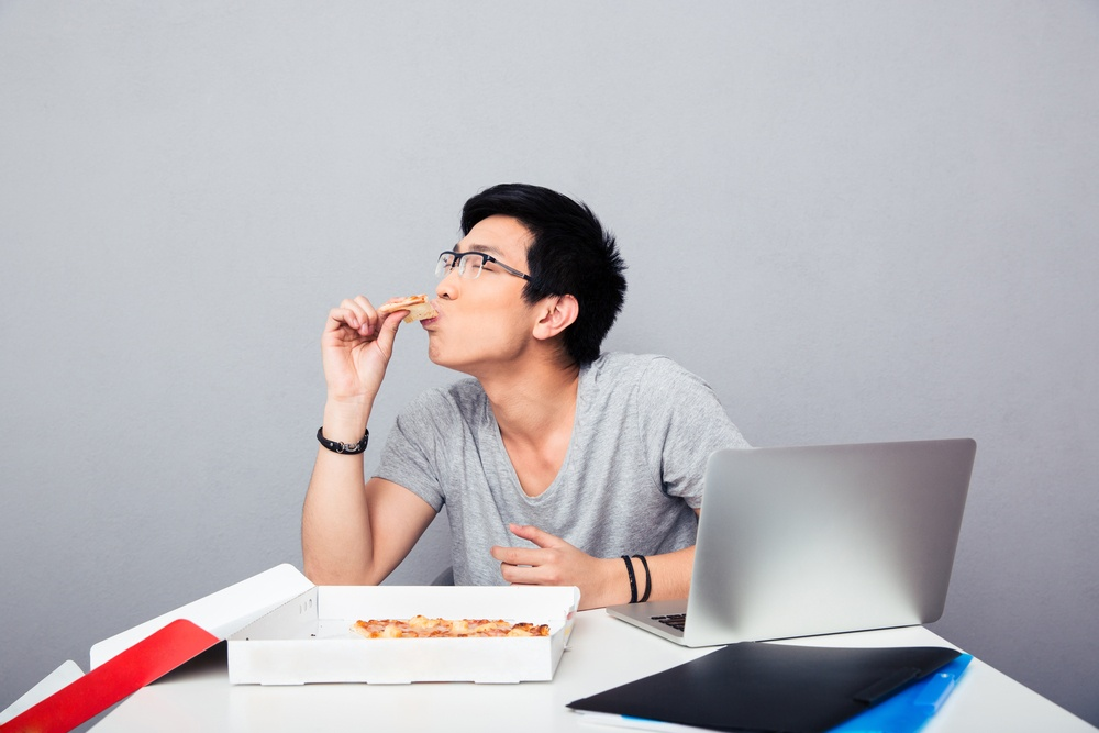 Handsome asian man sitting at the table and eating pizza over gray background