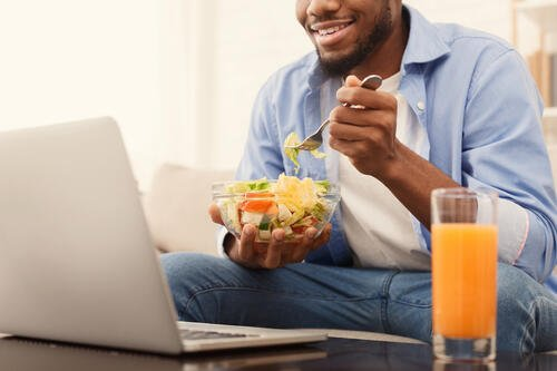 cheerful-african-american-man-eating-healthy-lunch-QT9DXS8