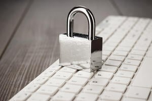 padlock-and-white-computer-keyboard-on-the-wooden--PWWDMLF